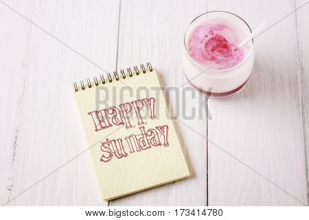 Berry smoothie and an inscription in notebook: Happy sunday. Closeup