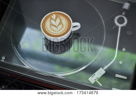 Coffee Cup With Latte Art On The Vinyl Player