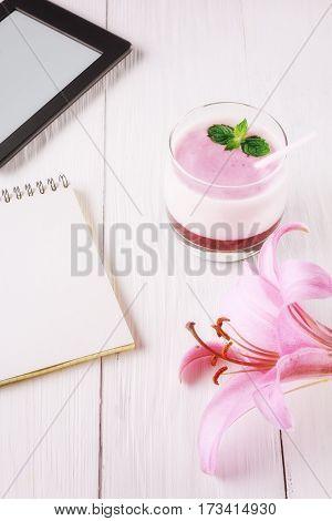 Berry smoothie with yogurt and eBook. Closeup