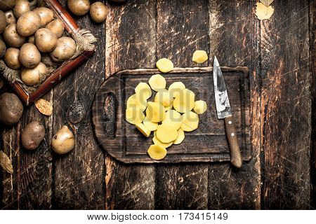 The Sliced Potatoes On An Old Wooden Board. On Wooden Background.