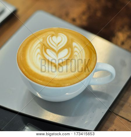 Coffee Cup With Latte Art On The Modern Scale