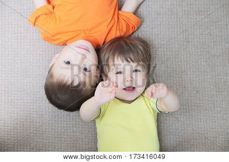Happy Children lying down on carpet happiness childhood concept little boy and little girl brother and sister indoor