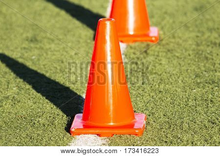Orange cones on a green turf field up close