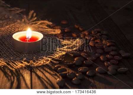 The candle burns near the coffee beans