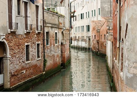 The river flows through the narrow streets of Venice between old houses in Italy