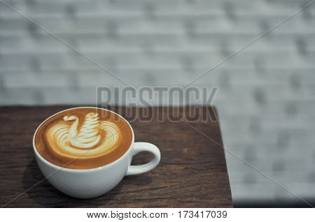 Coffee Cup With Latte Art Swan Pattern On The Wood Table