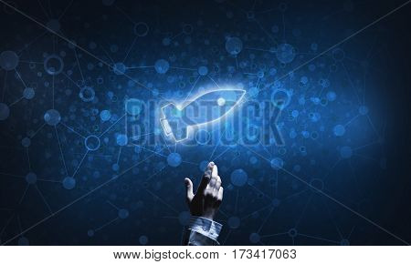 Mans hand pointing to light rocket on dark background
