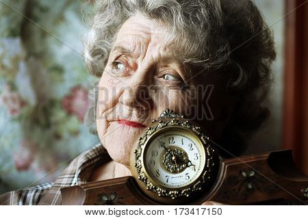 Thoughtful grandmother with clock on a dark background