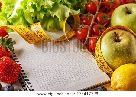 Fresh organic vegetables and fruits, open blank notebook and pen on wooden background. Healthy food and healthy life concept.