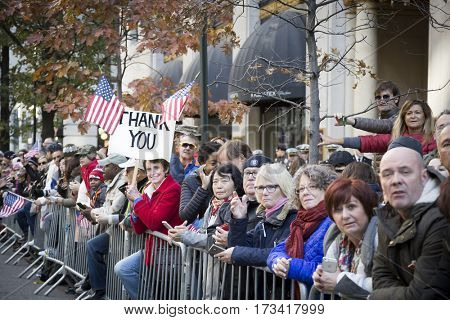 NEW YORK - 11 NOV 2016: A woman holding a Thank You sign with American Flags cheers from the sidewalk for the annual Americas Parade up 5th Avenue on Veterans Day in Manhattan.