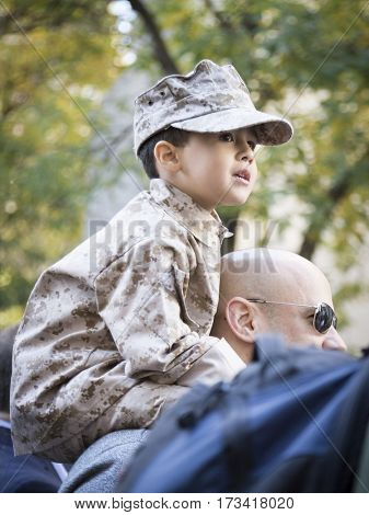 NEW YORK - 11 NOV 2016: A young boy wearing a camouflage uniform sits on the shoulders of a vet marching in the annual Americas Parade up 5th Avenue on Veterans Day in Manhattan.