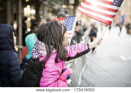 NEW YORK - 11 NOV 2016: An young girl waves an American Flag from the sidewalk for the annual Americas Parade up 5th Avenue on Veterans Day in Manhattan.