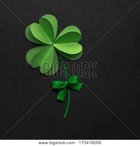 Creative St. Patricks Day concept photo of a shamrock made of paper on black background.