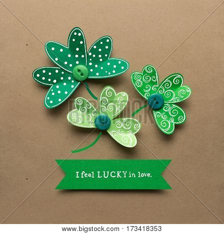 Creative St. Patricks Day concept photo of shamrocks made of paper on brown background.