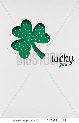 Creative St. Patricks Day concept photo of a shamrock made of paper on white background.