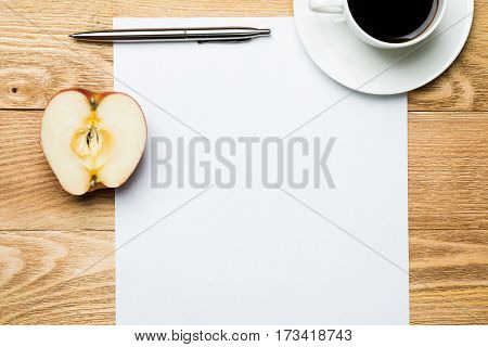 White blank paper with cup of coffee on wooden table