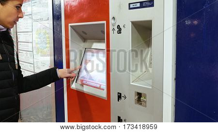 Hamburg, Germany - October, 10, 2016: Ticket machine in metro subway underground tube is being used by young lady. Woman buys tickets at public transportation station self service ticket machine.