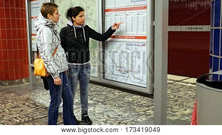 Hamburg, Germany - October, 10, 2016: Two women looking at subway metro underground tube map on train station. Tourists use public transportation subway metro system in a big European city.