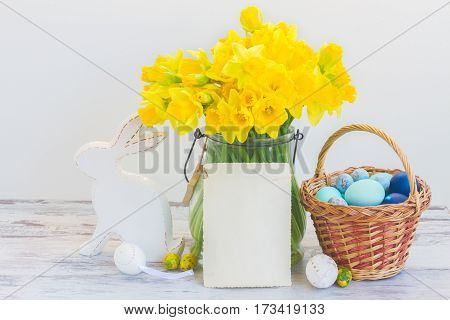 Easter eggs hunt - white rabbit, basket with painted eggs and daffodils bouquet, copy space on white paper note