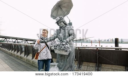 Hamburg, Germany - October, 10, 2016: Living statue street performer in Hamburg port poses with tourist to take a photo. Living statues acting is a popular way to entertain passersby and tourists.