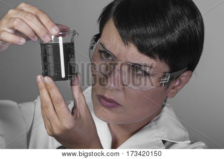 Analysis, Brunette woman in a laboratory, scientist studying a glass jar, wearing a white coat