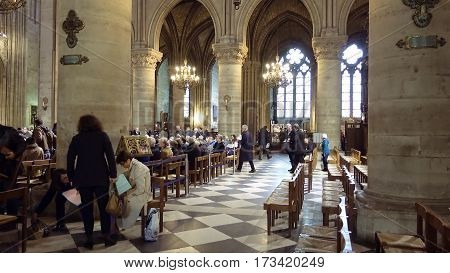 Paris, France - October, 14, 2016: Notre Dame de Paris cathedral interior with prayers and tourist visitor getting ready to listen a sermon from a priest.