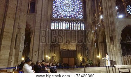 Paris, France - October, 14, 2016: Notre Dame de Paris cathedral interior with prayers listening a sermon from a French cardinal Andre Vingt-Trois.
