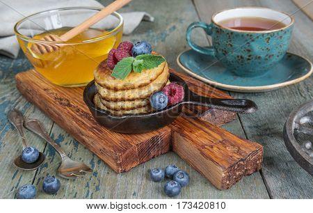 Breakfast in rustic style: pancakes in cast-iron frying pans honey fresh berries and black tea