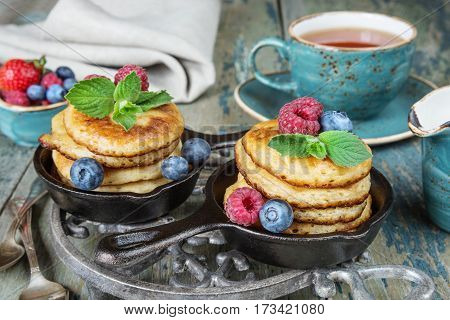 Breakfast of pancakes in cast-iron frying pans fresh berries and black tea in rustic style