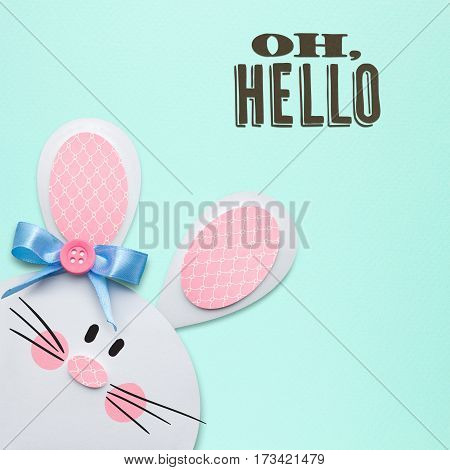 Creative easter concept photo of a rabbit made of paper on mint background.