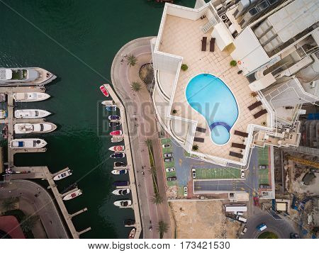 Pool filled with blue water, stand near some brown chairs. Below you can see a Marina with yachts and sailing boats