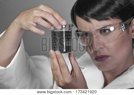Experiment, Brunette woman in a laboratory, scientist studying a glass jar, wearing a white coat