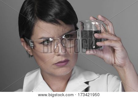 Brunette woman in a laboratory, scientist studying a glass jar, wearing a white coat