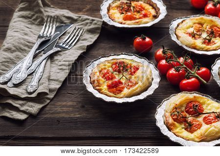 Fresh homemade tarts with cherry tomatoes and goat cheese on rustic wooden background.