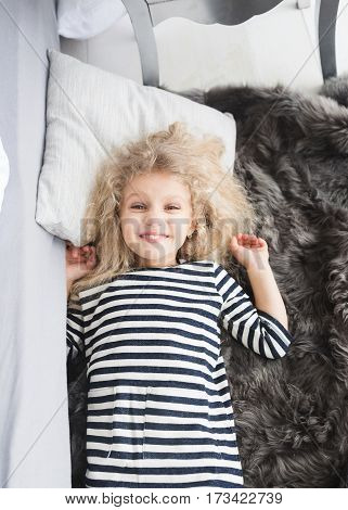 Little girl with white curly hair in a striped vestin bed. Little girl having fun. Girl pretending to sleep.