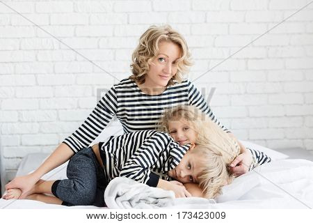 Mother and two children in the bedroom on the bed. Mother son and daughter. Family in the striped vest. Mom hugging their children. Brother and sister