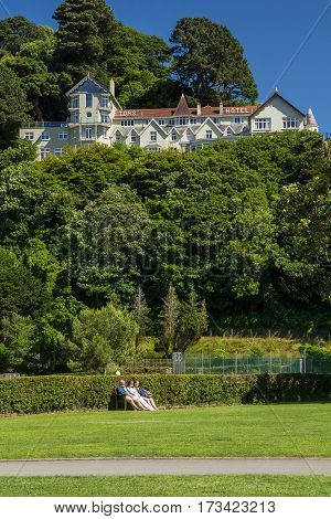 Lynmouth Devon England 13 July 2016: Tors Hotel on the hill and people have a rest at the bottom on the bench