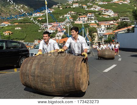 ESTREITO DE CAMARA DE LOBOS PORTUGAL - SEPTEMBER 10 2016: Men wearing in traditional costumes roll barrels during parade at Madeira Wine Festival in Estreito de Camara de Lobos Madeira Portugal. The Madeira Wine Festival honors the grape harvest with a ce