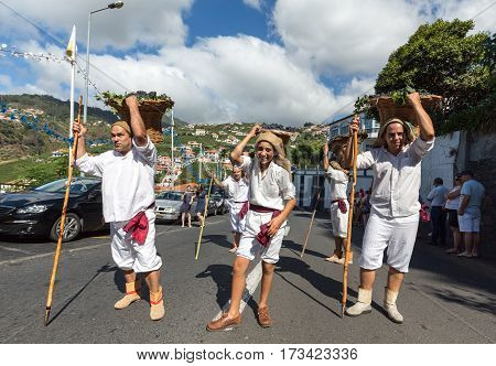 ESTREITO DE CAMARA DE LOBOS PORTUGAL - SEPTEMBER 10 2016: Men wearing in traditional costumes carry baskets of grapes at Madeira Wine Festival in Estreito de Camara de Lobos Madeira Portugal. The Madeira Wine Festival honors the grape harvest with a celeb
