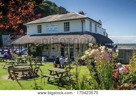 Lynmouth North Devon England 13 July 2016: Restaurant and Accommodations - Rock House. People sit at tables in the courtyard