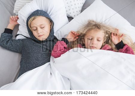 Little girl with white curly hair in red pajamas and a little boy with blond hair in a gray pajamas sleeping in bed. Brother and sister