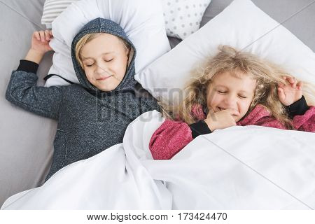 Little girl with white curly hair in red pajamas and a little boy with blond hair in a gray pajamas sleeping in bed. Brother and sister. Children pretending to sleep