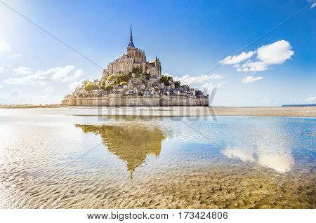 Panoramic View Of Famous Le Mont Saint-michel Tidal Island On A Sunny Day With Blue Sky And Clouds,
