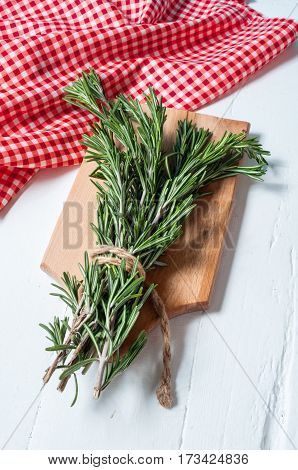 Organic bunch of fresh rosemary on white table.