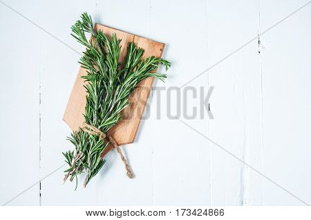 Organic bunch of fresh rosemary on white table. Top view and copyspace