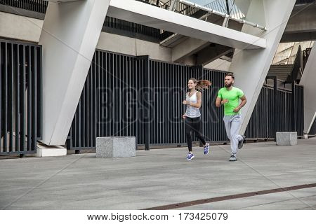 Active happy young couple jogging side by side in an urban street during their daily workout in a health and fitness concept. using sport watch.