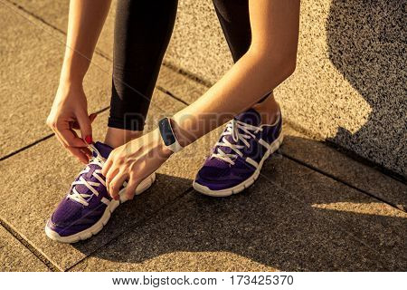 Running shoes. Barefoot running shoes closeup. Female athlete tying laces for jogging on road in minimalistic barefoot running shoes. Runner getting ready for training. Sport lifestyle.