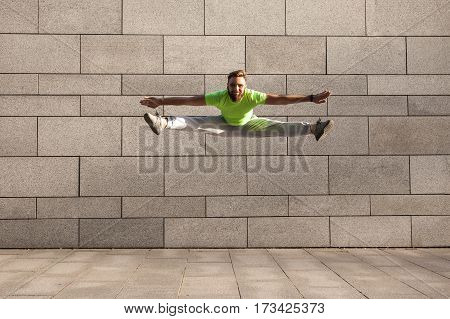 Pose of a male sportsman jumping with spread legs on the gray city background.