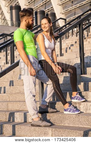 Young couple resting after running together in the city