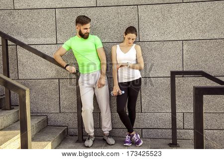 Young sporty couple are resting and check their fitness watch together drinking water. sport and technology concepts.